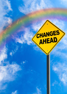 Changes Ahead sign against a blue sky with rainbow and copy space. Concept of situation changing for the better. Vertical orientation.