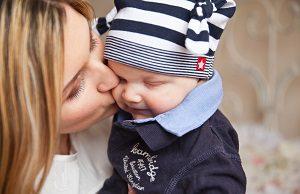 Mom kissing baby boy.