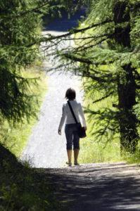 Woman walking on path in woody area