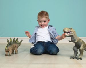 3 yr. old boy with toy dinosaurs